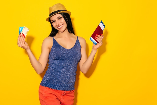 Joven estudiante mujer emocionada sonriente sosteniendo pasaporte boleto de embarque y tarjeta de crédito aislado