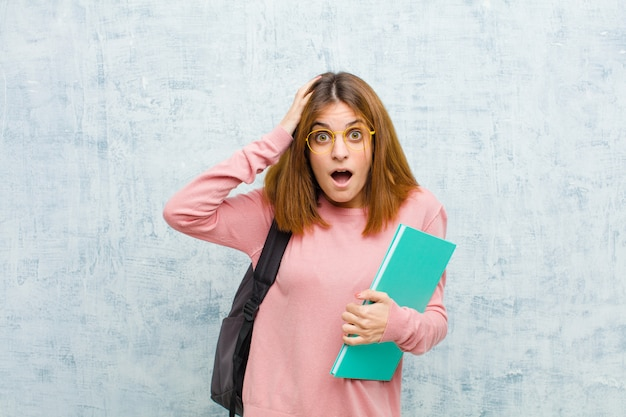 Joven estudiante mujer emocionada y sorprendida, con la boca abierta con ambas manos en la cabeza, sintiéndose como un ganador afortunado