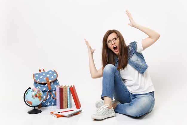 Joven estudiante mujer enojada conmocionada en ropa de mezclilla gritando extendiendo las manos sentado cerca de libros de escuela de mochila de globo