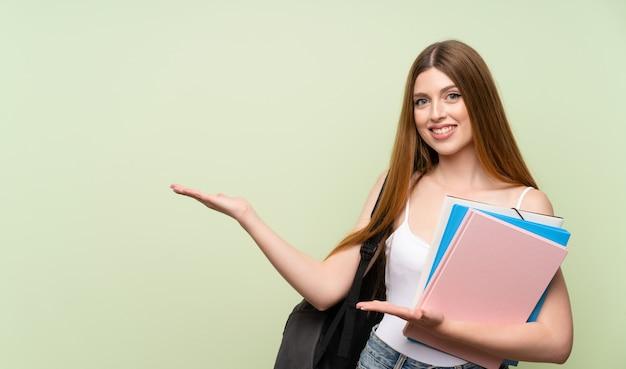 Joven estudiante mujer extendiendo las manos al lado para invitar a venir