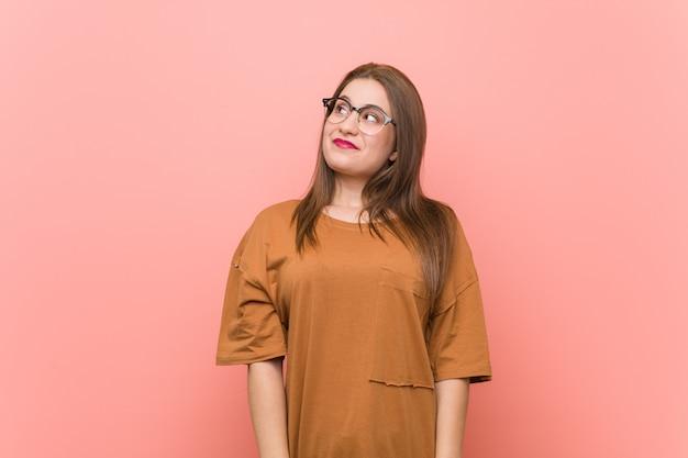Joven estudiante mujer con gafas soñando con lograr objetivos y propósitos