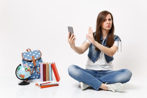 Joven estudiante mujer insatisfecha en cuestión mantenga teléfono móvil mostrar gesto de parada con la palma sentarse cerca de los libros de la escuela mochila globo aislado