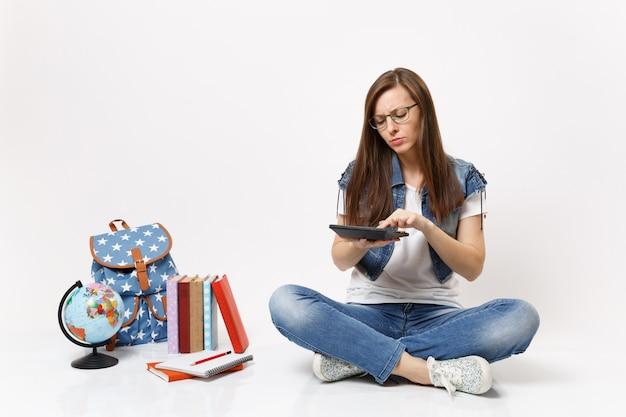 Joven estudiante mujer inteligente concentrada sosteniendo usando calculadora resolviendo ecuaciones matemáticas sentado cerca del globo, mochila, libros escolares aislados