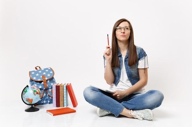 Joven estudiante mujer inteligente pensativa pensando en un nuevo pensamiento, idea mirando hacia arriba apuntando con lápiz cerca del globo, mochila, libros aislados