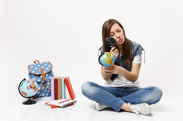 Joven estudiante mujer interesada inteligente mirando globo con lupa aprendiendo sentado cerca de la mochila, libros escolares aislados