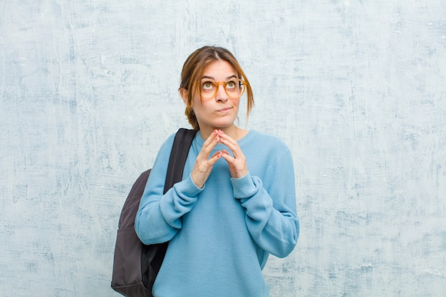 Joven estudiante mujer intrigando y conspirando, pensando trucos y trucos tortuosos, astuto y traicionando contra la pared de la pared del grunge