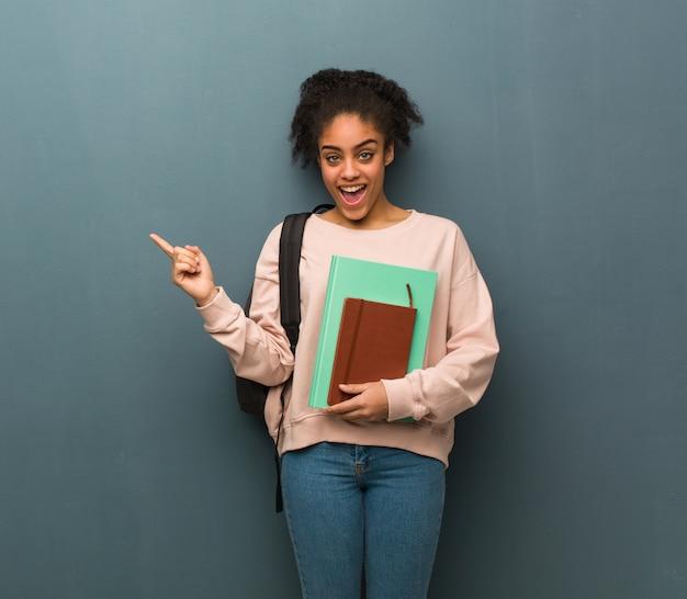 Joven estudiante mujer negra apuntando hacia el lado con el dedo. ella está sosteniendo libros.
