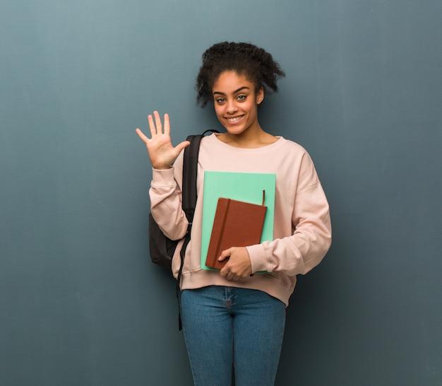 Joven estudiante mujer negra mostrando el número cinco. ella está sosteniendo libros.