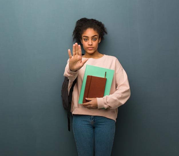 Joven estudiante mujer negra poniendo la mano en el frente. ella está sosteniendo libros.