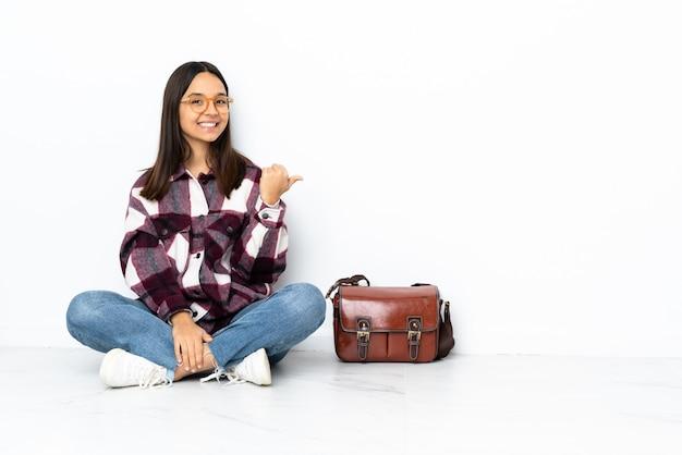 Joven estudiante mujer sentada en el suelo apuntando hacia un lado para presentar un producto