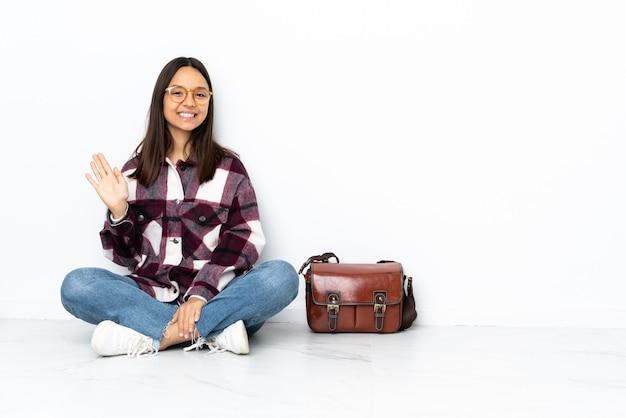 Joven estudiante mujer sentada en el suelo saludando con la mano con expresión feliz