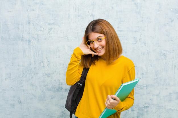 Joven estudiante mujer sonriendo alegremente y señalando mientras hace una llamada más tarde gesto, hablando por teléfono