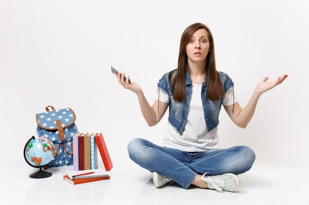 Joven estudiante mujer sorprendida y perpleja sosteniendo el teléfono móvil, extendiendo la mano, sentado cerca del globo, mochila, libros escolares aislados