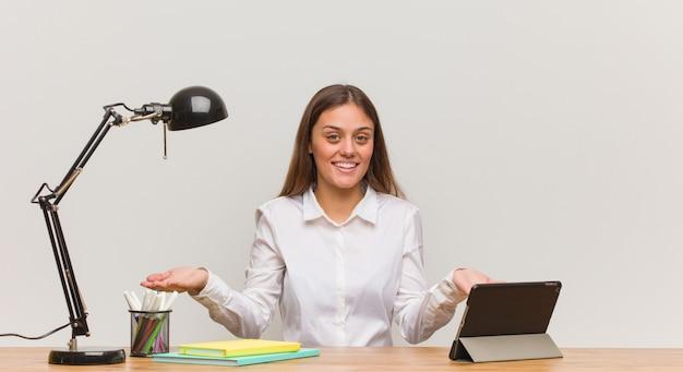 Joven estudiante mujer trabajando en su escritorio invitando a venir