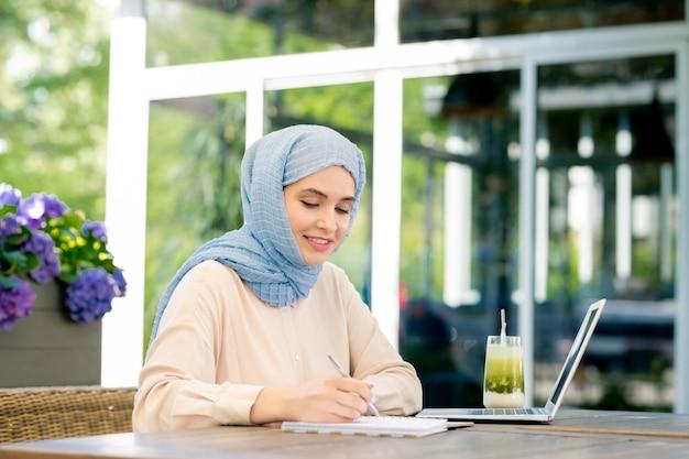 Joven estudiante musulmán en hijab haciendo notas de trabajo o haciendo tareas en casa al aire libre