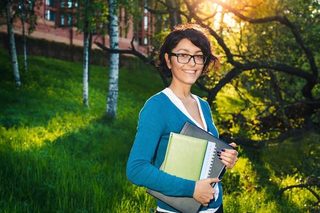 Joven estudiante con notebook. en línea estudiando al aire libre.