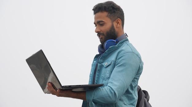 Un joven estudiante con ordenador portátil y auriculares concepto de educación