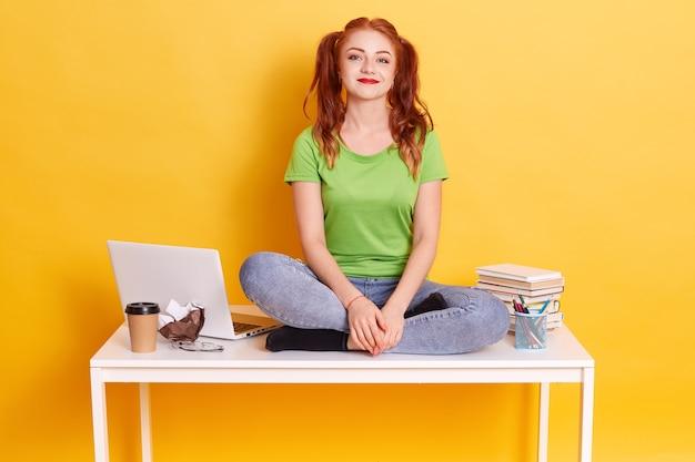 Joven estudiante de pelo rojo sentado en la mesa blanca con las piernas cruzadas, divertida dama con coletas estudiando, mirando a la cámara