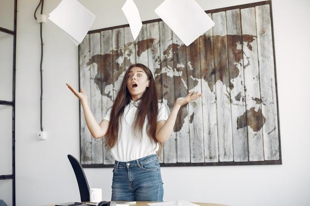 Joven estudiante de pie en la oficina y arroja los documentos