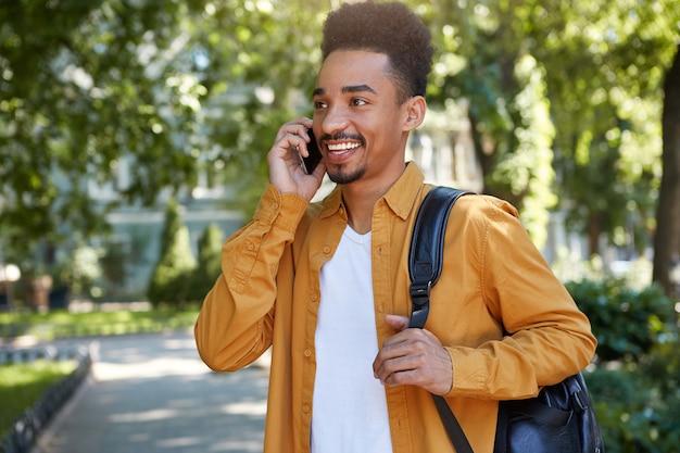 Joven estudiante de piel oscura sonriente caminando en el parque, hablando por teléfono inteligente, esperando a su amigo, viste con camisa amarilla, mirando a otro lado y sonriendo ampliamente.