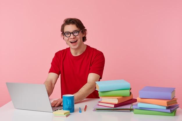 Joven estudiante positivo en gafas viste camiseta roja, se sienta junto a la mesa y trabaja con libros y cuaderno, preparado para el examen, con mirada seria, sonrisas amplias aisladas sobre fondo rosa.