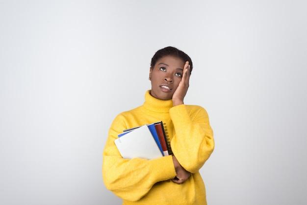 Joven estudiante preocupado de la mano en la cabeza y mirando hacia arriba