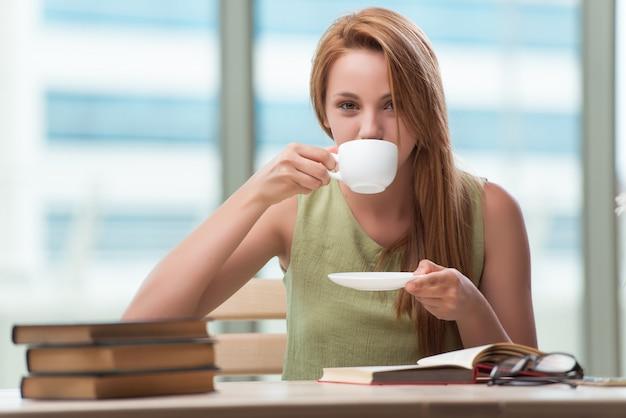 Joven estudiante preparándose para exámenes tomando té