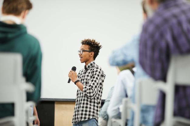 Joven estudiante presentando su proyecto de inicio en conferencia