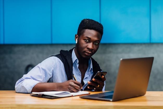 Joven estudiante que se prepara con la computadora portátil antes de los exámenes en la cocina de casa. estilo de vida.