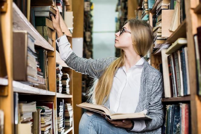 Joven estudiante recogiendo libros de estantería