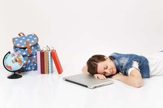 Joven estudiante relajada en ropa de mezclilla durmiendo en la computadora portátil que miente cerca del globo, mochila, libros escolares