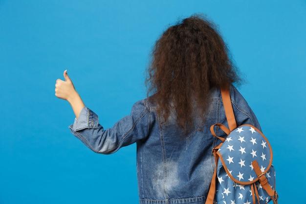 Joven estudiante en ropa de mezclilla y mochila tiene libros aislados en la pared azul