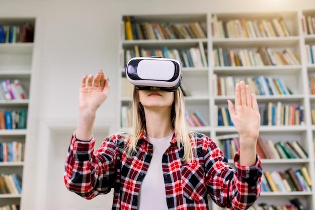 Joven estudiante rubia caucásica trabajando con simulador de realidad virtual en la biblioteca.
