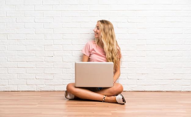 Joven estudiante rubia con una computadora portátil en el piso mirando hacia el lado
