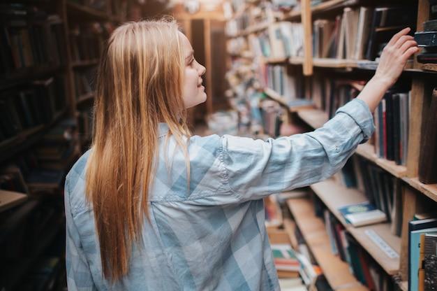 Joven estudiante rubia está eligiendo un libro de la estantería. ella necesita encontrar el libro adecuado para prepararse para el examen. de cerca.