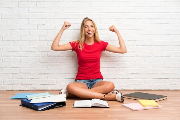 Joven estudiante rubia con muchos libros en el piso celebrando una victoria
