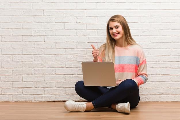 Joven estudiante rusa mujer sentada sonriendo y levantando el pulgar