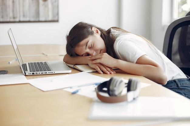 Joven estudiante sentada en la mesa y durmiendo