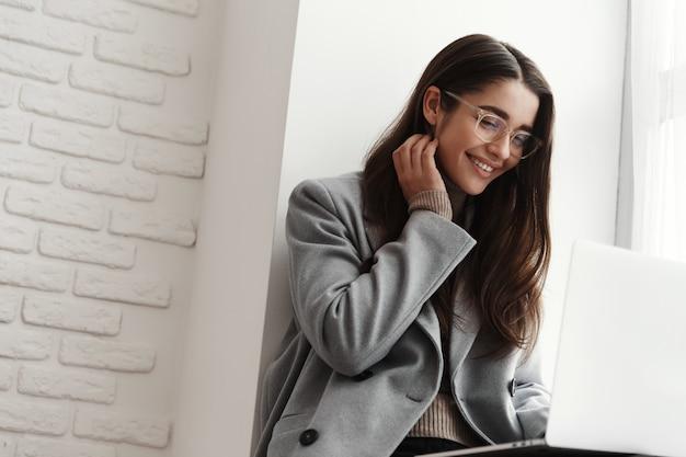 Joven estudiante sentada en la ventana del campus y usando una computadora portátil, sonriendo feliz.