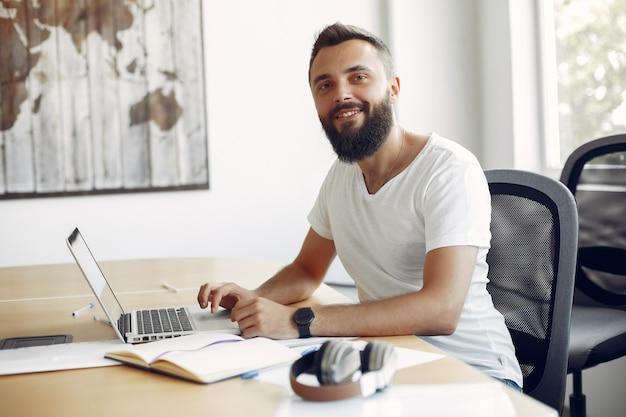 Joven estudiante sentado en la mesa y usar la computadora portátil