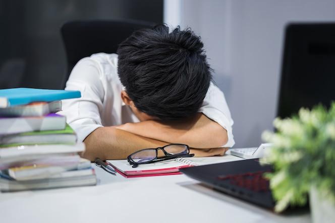 Joven estudiante sentado y durmiendo en el escritorio con el libro y la computadora portátil