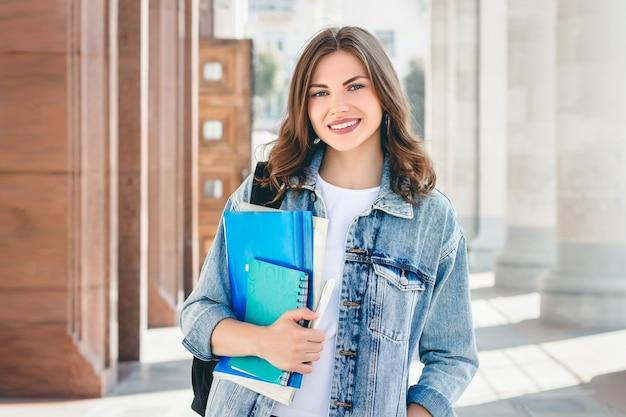 Joven estudiante sonriente contra la universidad. linda chica estudiante tiene carpetas y cuadernos en las manos. aprendizaje, educacion