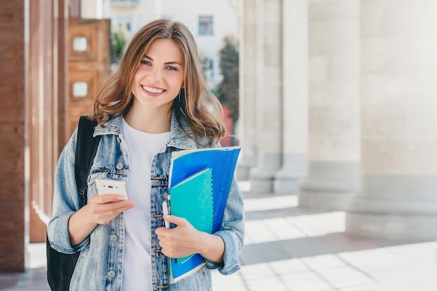 Joven estudiante sonriente contra la universidad. linda chica estudiante tiene carpetas, cuadernos y teléfono móvil en las manos. aprendizaje, educacion