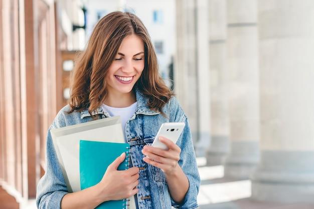 Joven estudiante sonriente contra la universidad. linda estudiante tiene carpetas, cuadernos y teléfono móvil y lee mensajes. aprendizaje, educacion