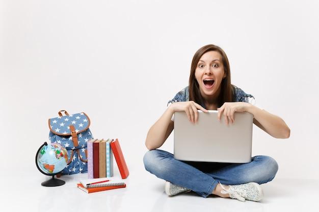 Joven estudiante sorprendida con la boca abierta sosteniendo aferrándose a la computadora portátil que se sienta cerca de los libros escolares de la mochila del globo aislados