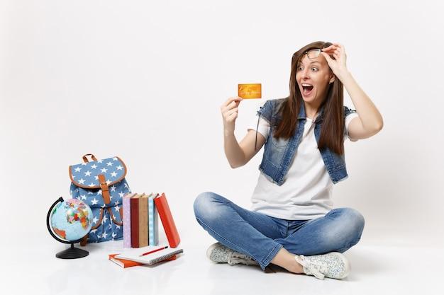 Joven estudiante sorprendida sorprendida con la boca abierta quitando los anteojos mirando en la tarjeta de crédito cerca de los libros escolares de la mochila del globo aislado