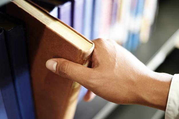 Joven estudiante sosteniendo un libro en la mano o elegir un libro en la estantería en el fondo de estanterías de la biblioteca - concepto de estudio de educación empresarial