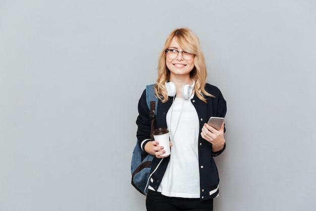 Joven estudiante sosteniendo la taza de café y teléfono inteligente