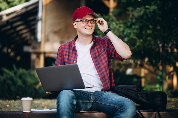 Joven estudiante trabajando en una computadora fuera del café en el parque