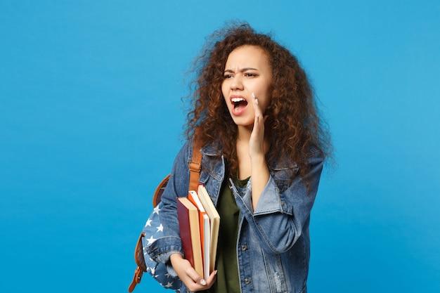 Joven estudiante triste en ropa de mezclilla y mochila tiene libros aislados en la pared azul Foto gratis